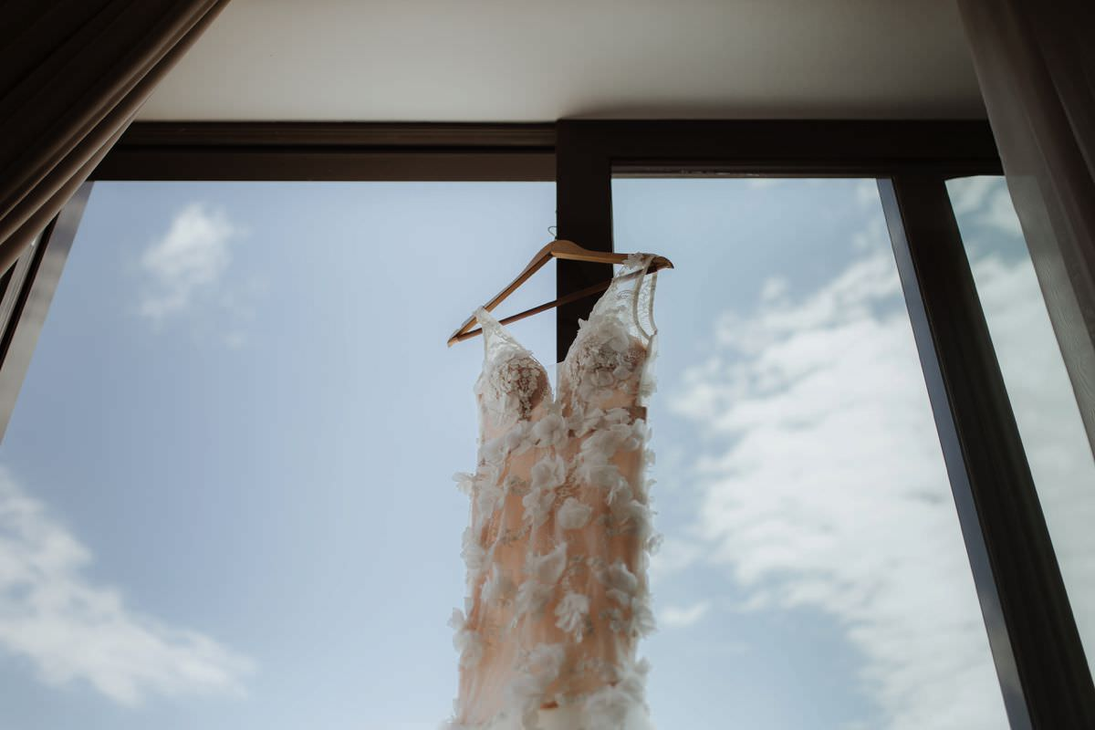 romantic wedding dress hanging on the window