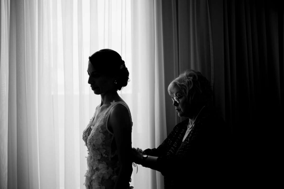 mother helping the bride to dreess